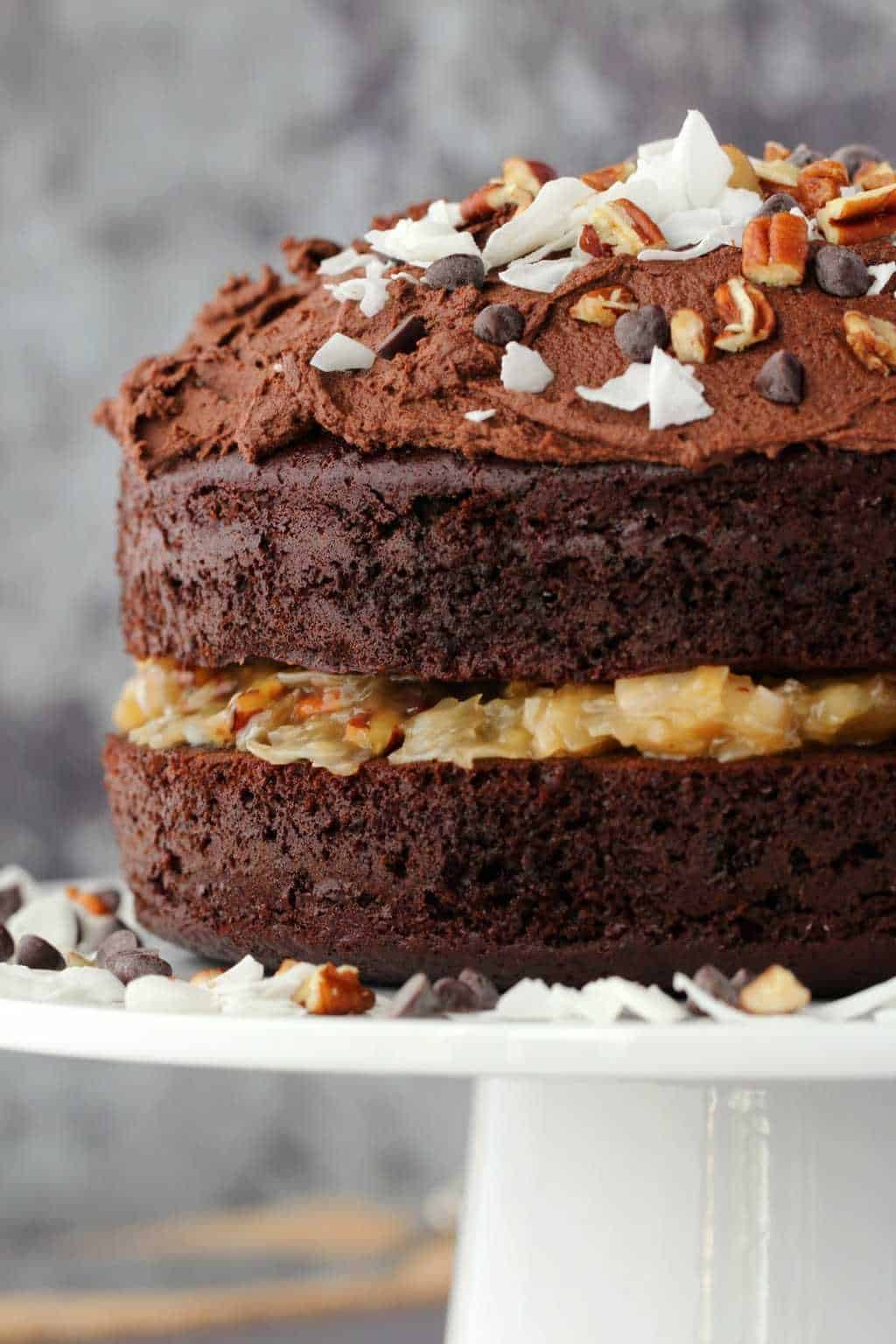 Vegan german chocolate cake decorated with coconut flakes, chopped pecans and chocolate chips on a white cake stand.
