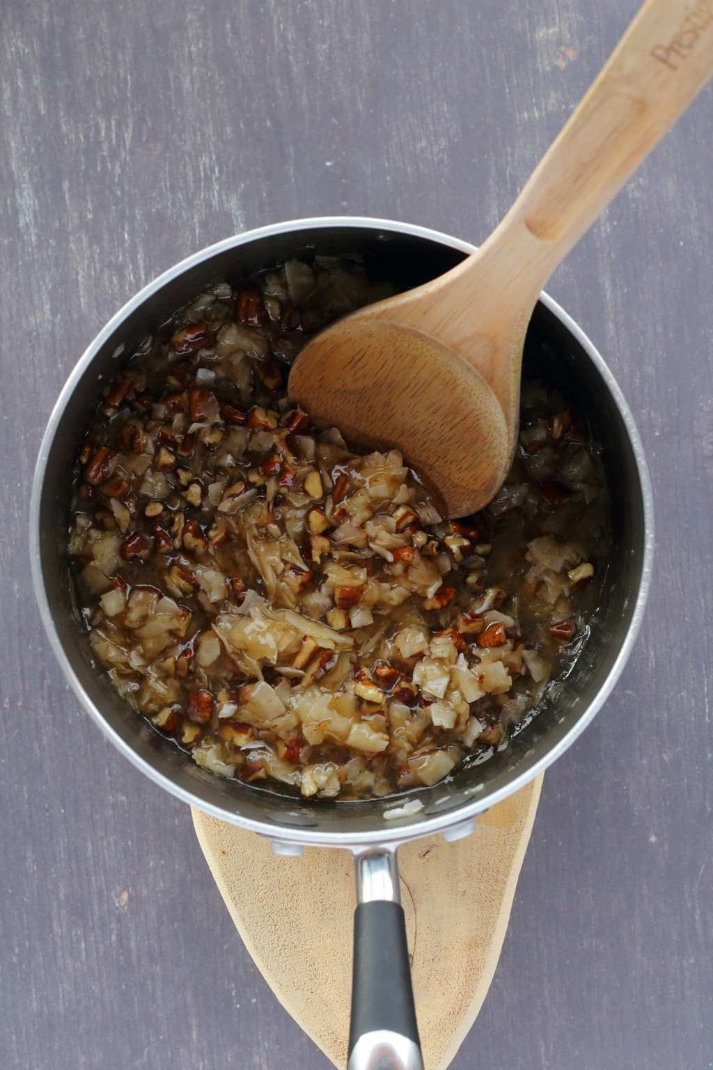 Coconut pecan filling for a vegan German chocolate cake in a saucepan with a wooden spoon.