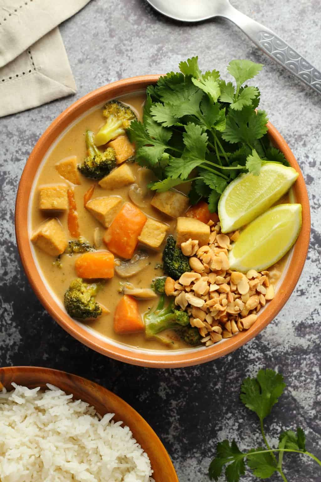 Massaman curry in a bowl topped with fresh lime and cilantro and crushed peanuts.