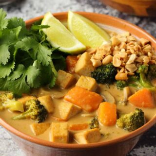 Vegan massaman curry with fresh lime and cilantro in a brown bowl.