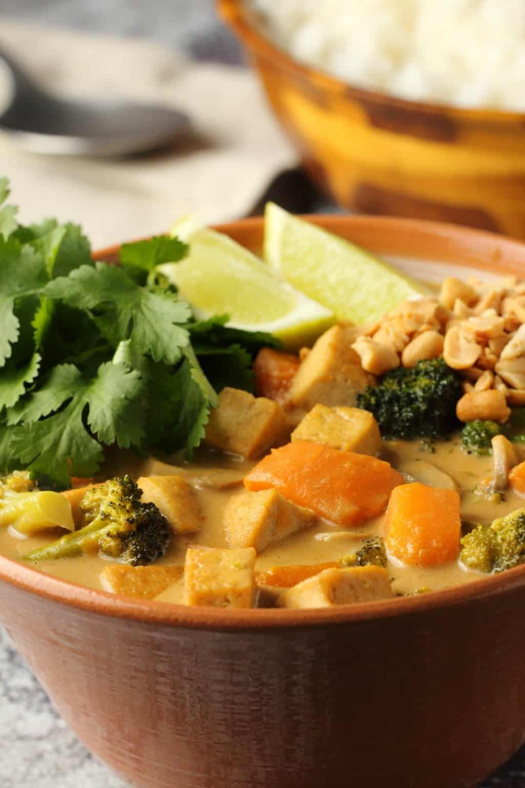 Vegan massaman curry in a bowl topped with crushed peanuts, fresh lime and cilantro.
