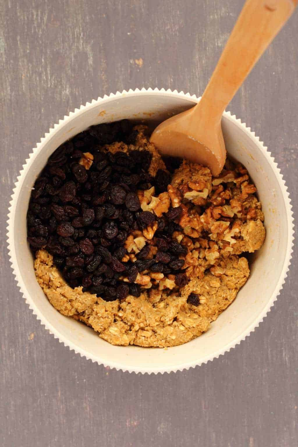 Cookie dough topped with raisins and walnuts in a mixing bowl with a wooden spoon.