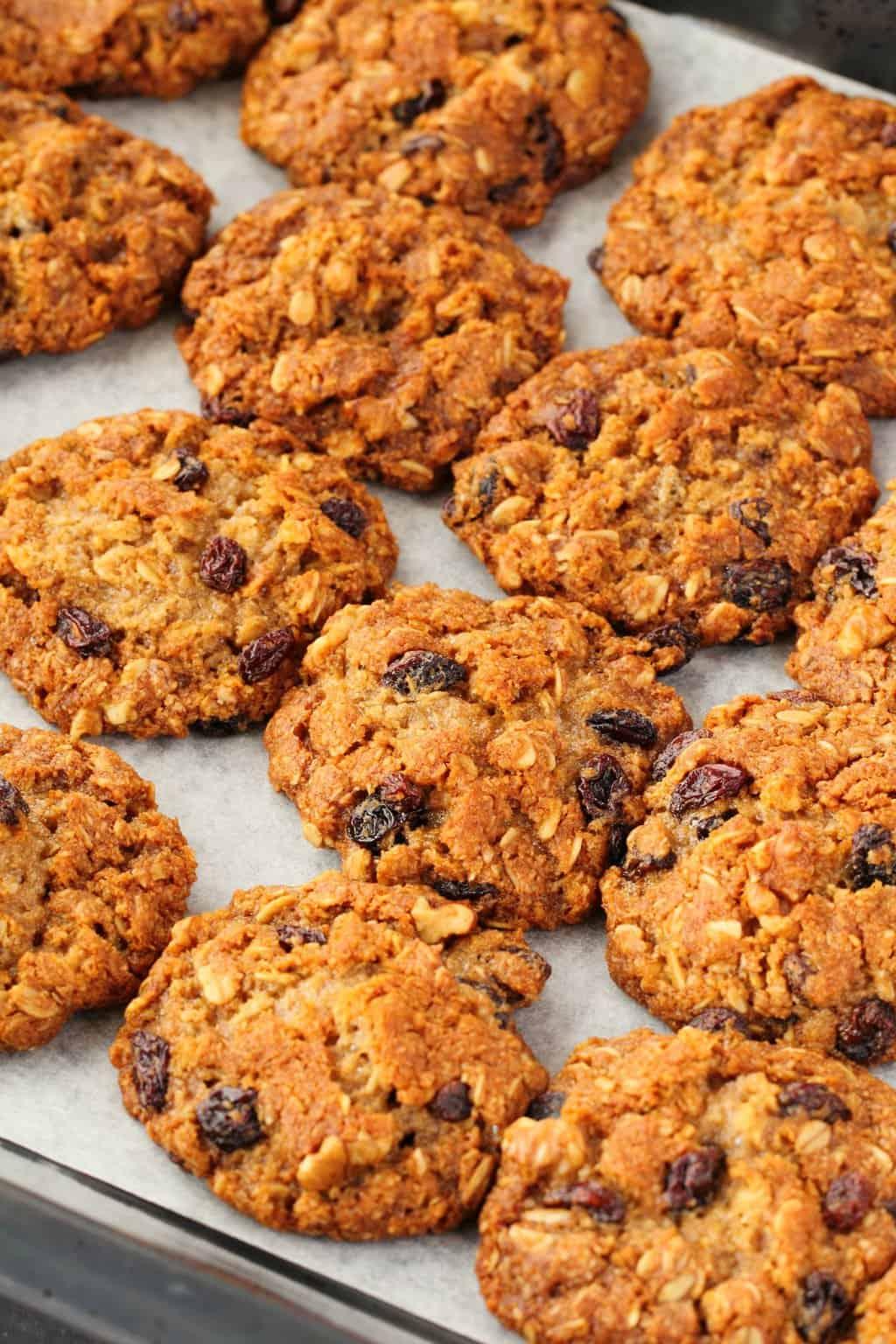 Freshly baked vegan oatmeal raisin cookies on a baking tray.