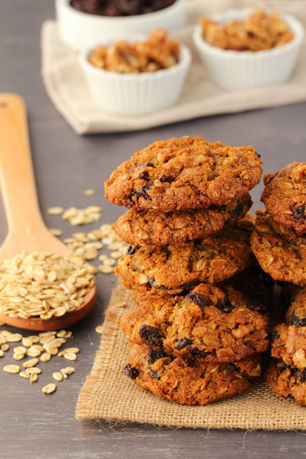 Vegan oatmeal raisin cookies stacked up on a woven napkin, scattered oats and a wooden spoon in the background.