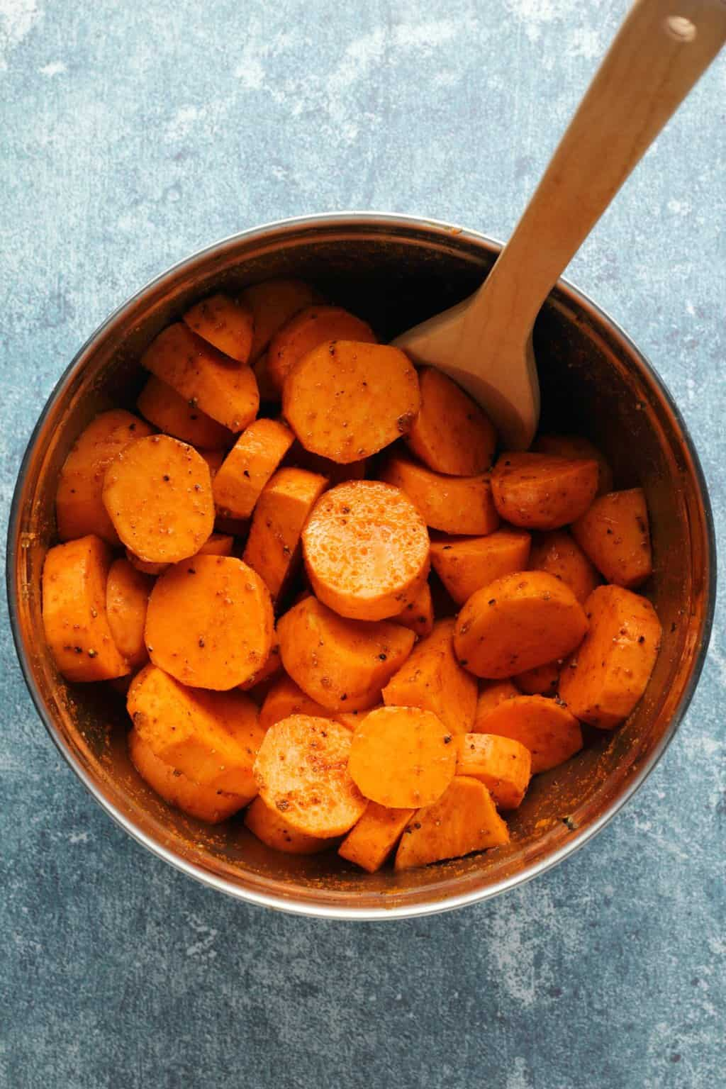 Sliced sweet potatoes in a silver bowl with a wooden spoon.