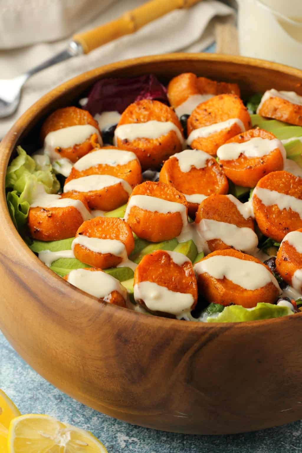 Vegan sweet potato salad topped with tahini dressing in a wooden salad bowl.