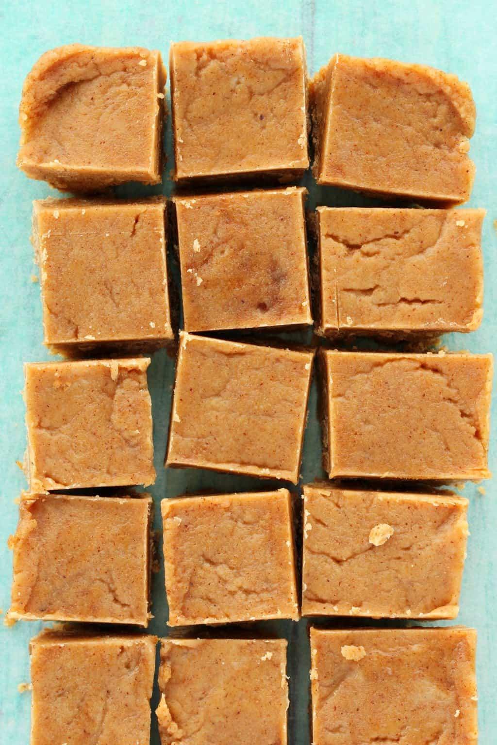 Vegan almond butter fudge cut into squares on parchment paper.
