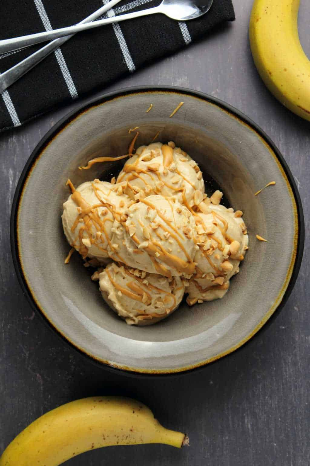 Peanut Butter Banana Ice Cream topped with drizzled peanut butter and crushed peanuts in a stone bowl.