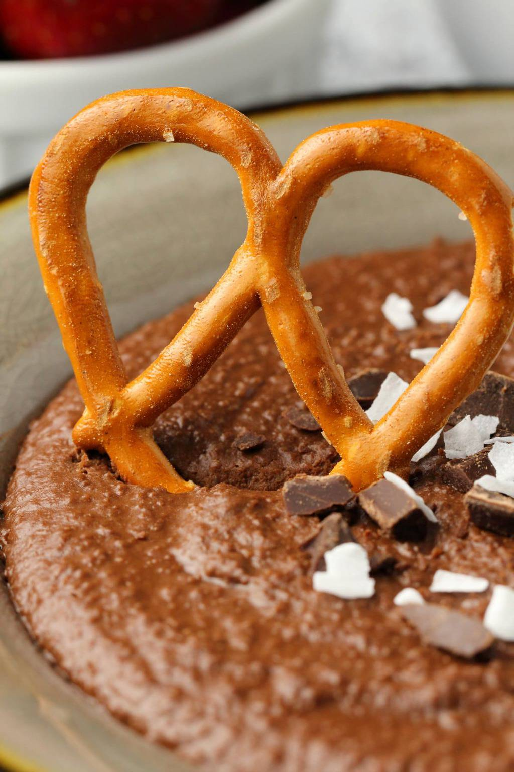 A pretzel dipping into a bowl of chocolate dessert hummus.