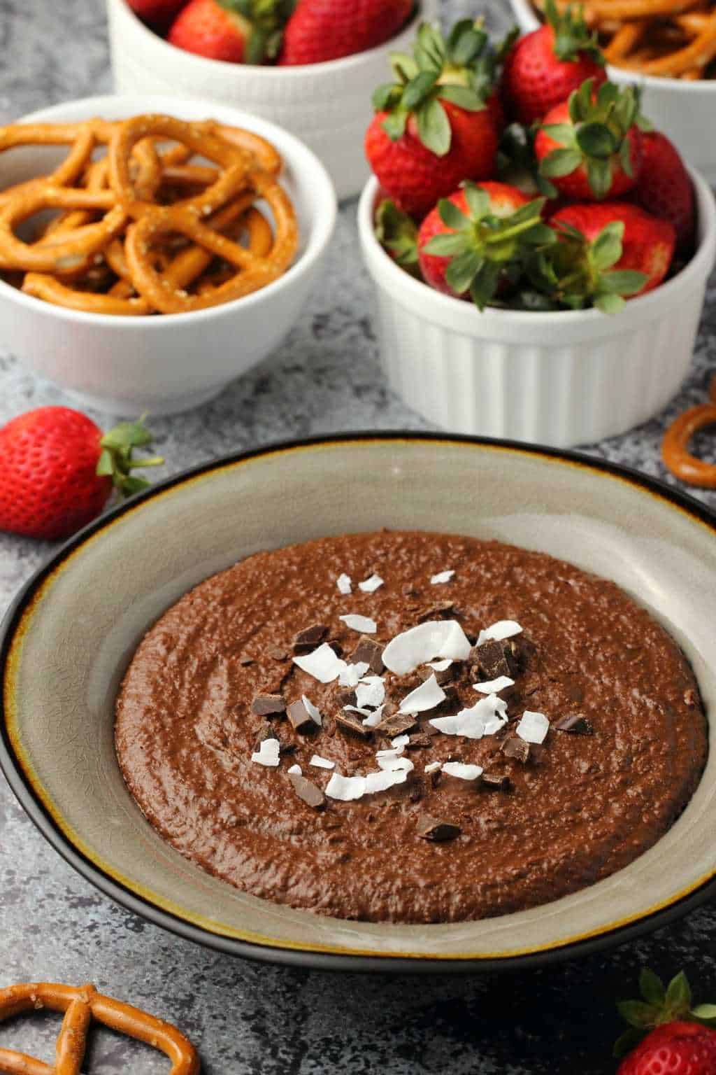 Chocolate Dessert Hummus topped with chocolate pieces and coconut flakes in a stone bowl.