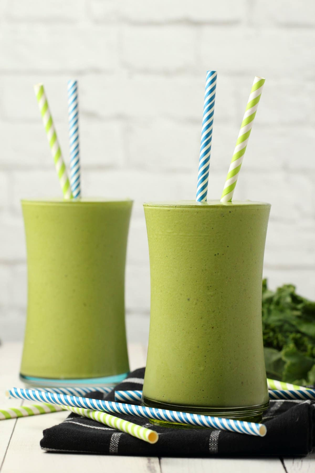Kale Smoothie in glasses with striped straws.