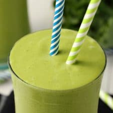 Kale Smoothie in a glass with straws.