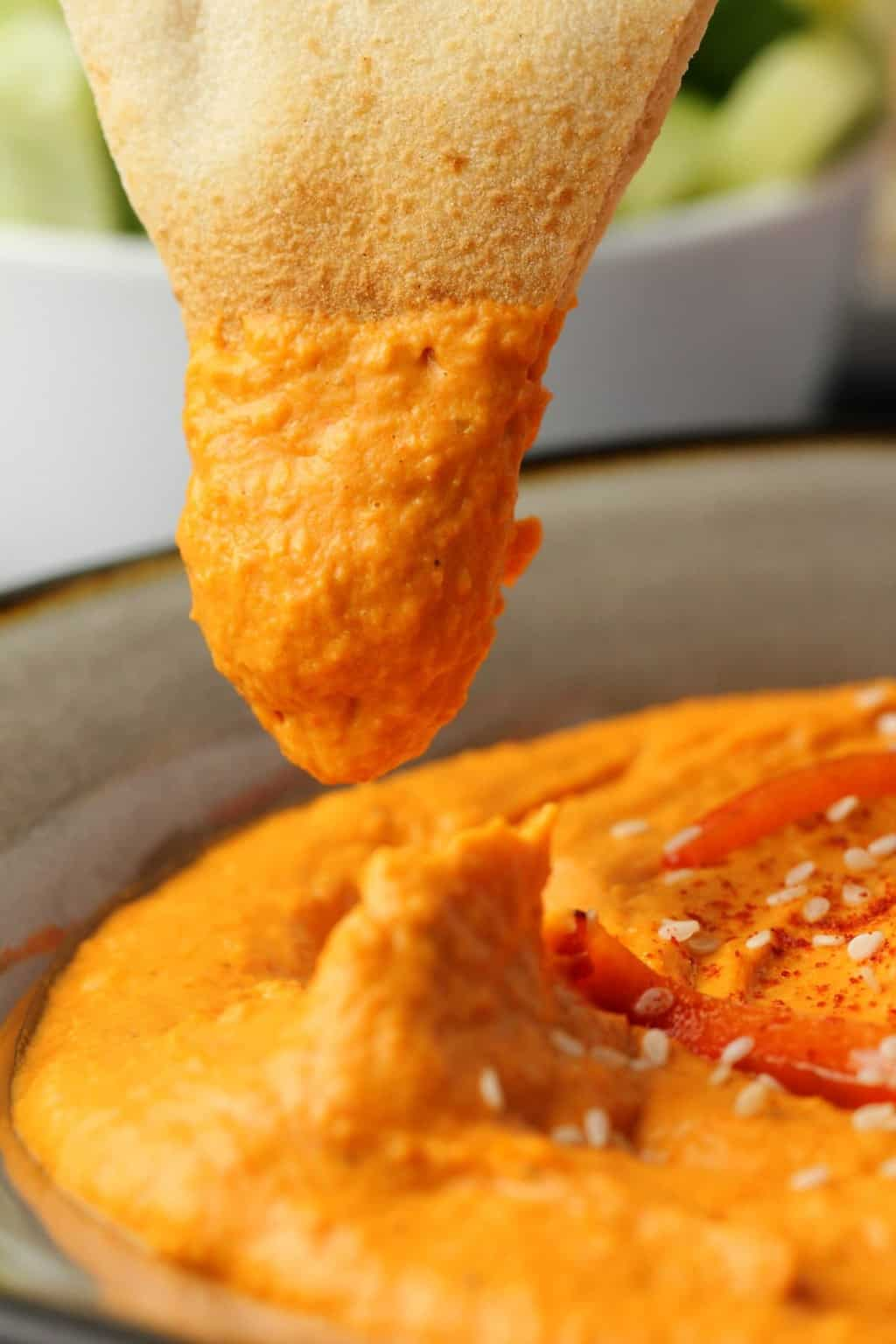 Pita bread dipping into a bowl of roasted red pepper hummus.