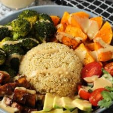 Vegan buddha bowl drizzled with sauce in a blue bowl.