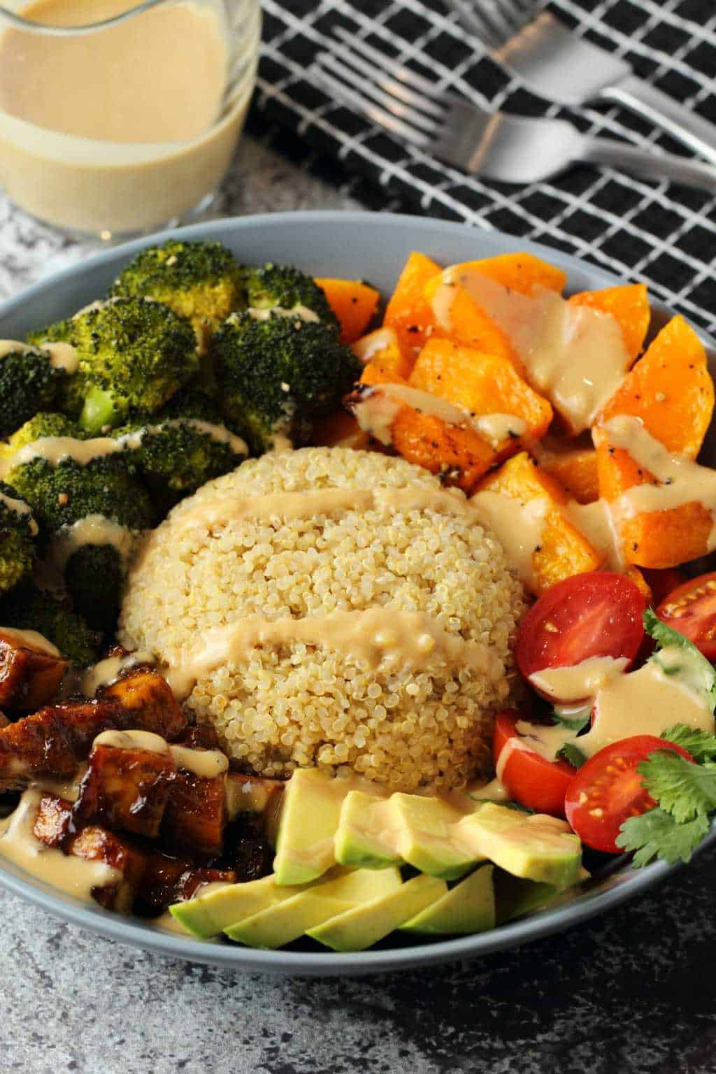 Bowl with quinoa, vegetables and tofu topped with a drizzled dressing.