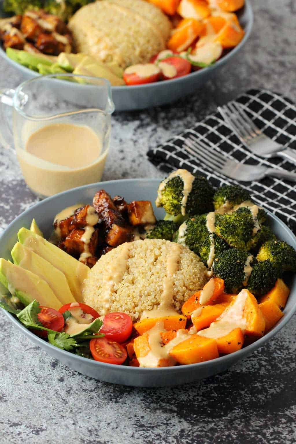 Vegan Buddha Bowl with quinoa, tofu and vegetables in a blue bowl.