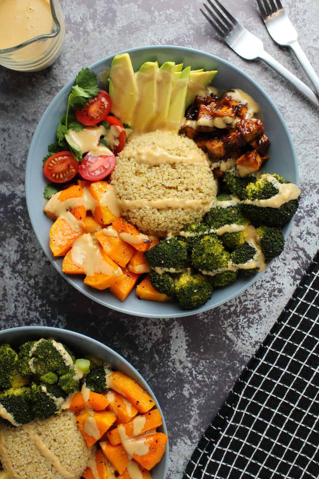 Buddha bowl with quinoa, tofu, vegetables and a drizzled dressing.