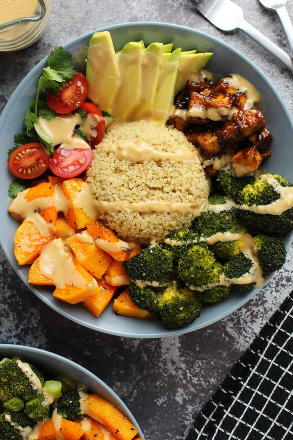 Vegan Buddha Bowl with quinoa and vegetables in a blue bowl.