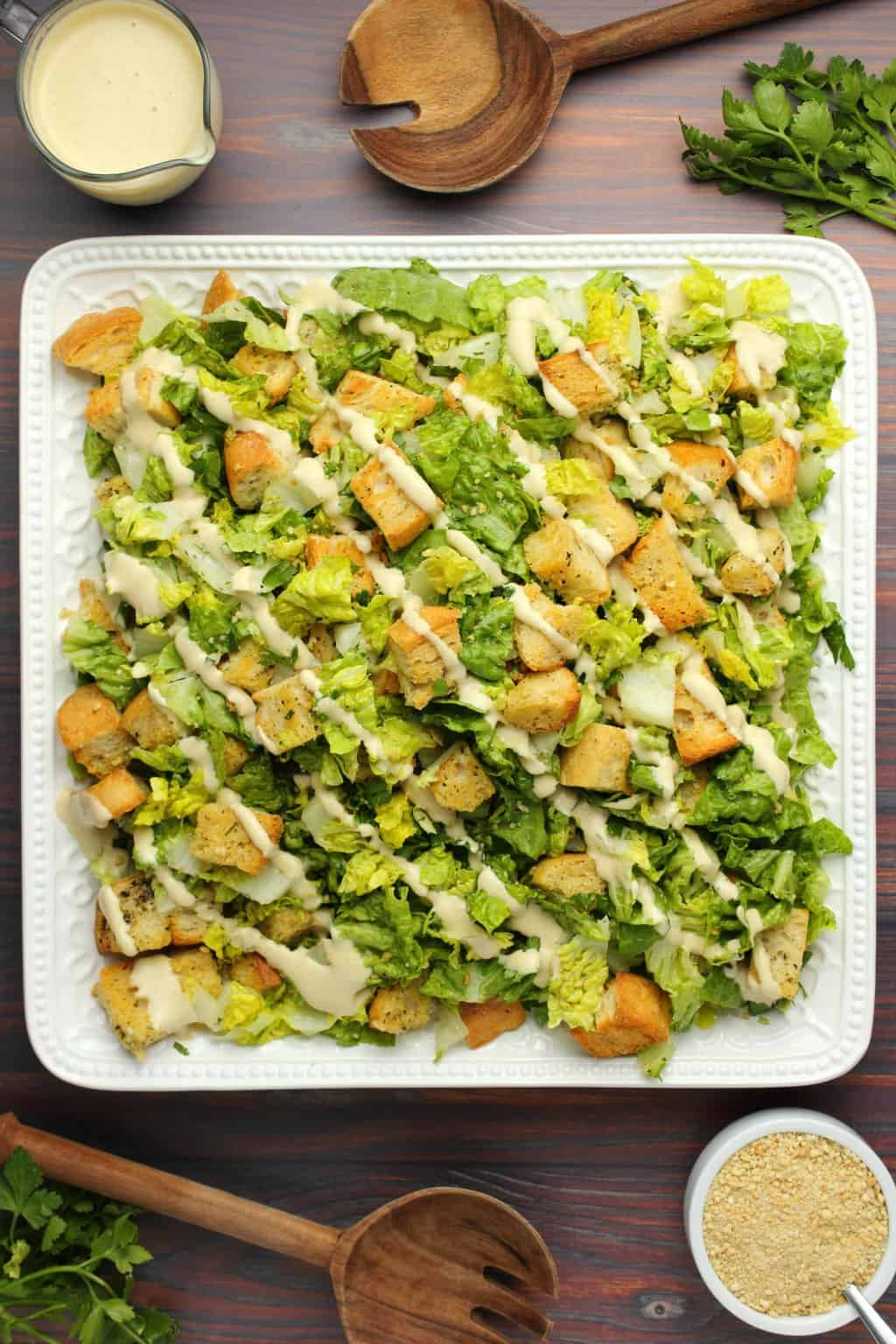 Vegan caesar salad topped with caesar dressing on a white salad platter.