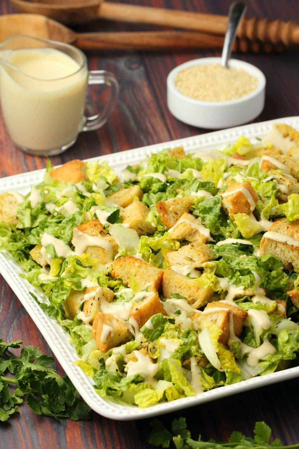 Vegan caesar salad topped with caesar dressing on a white salad platter.
