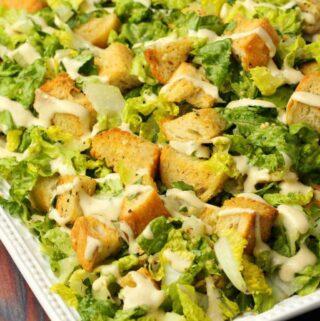 Vegan caesar salad in a white serving dish.