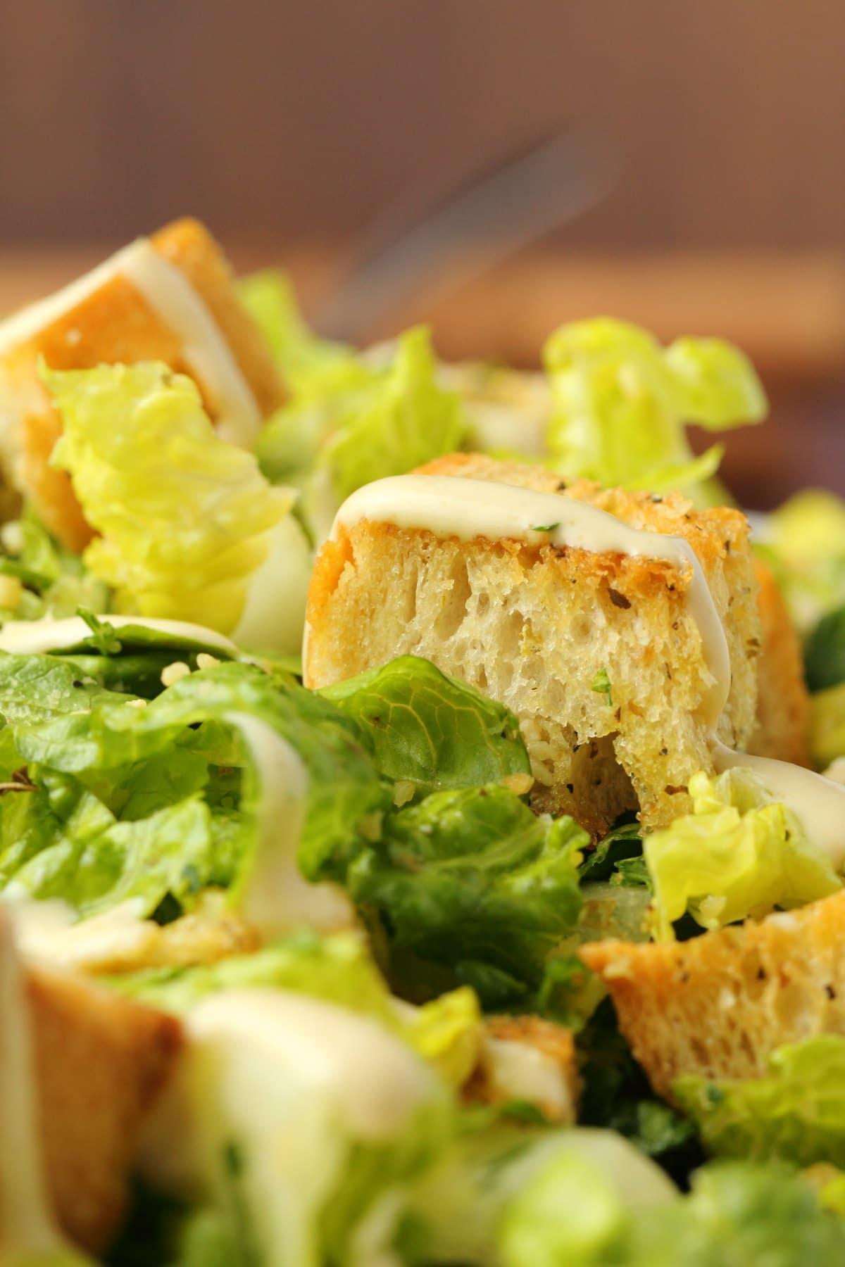 Vegan caesar salad topped with caesar dressing.