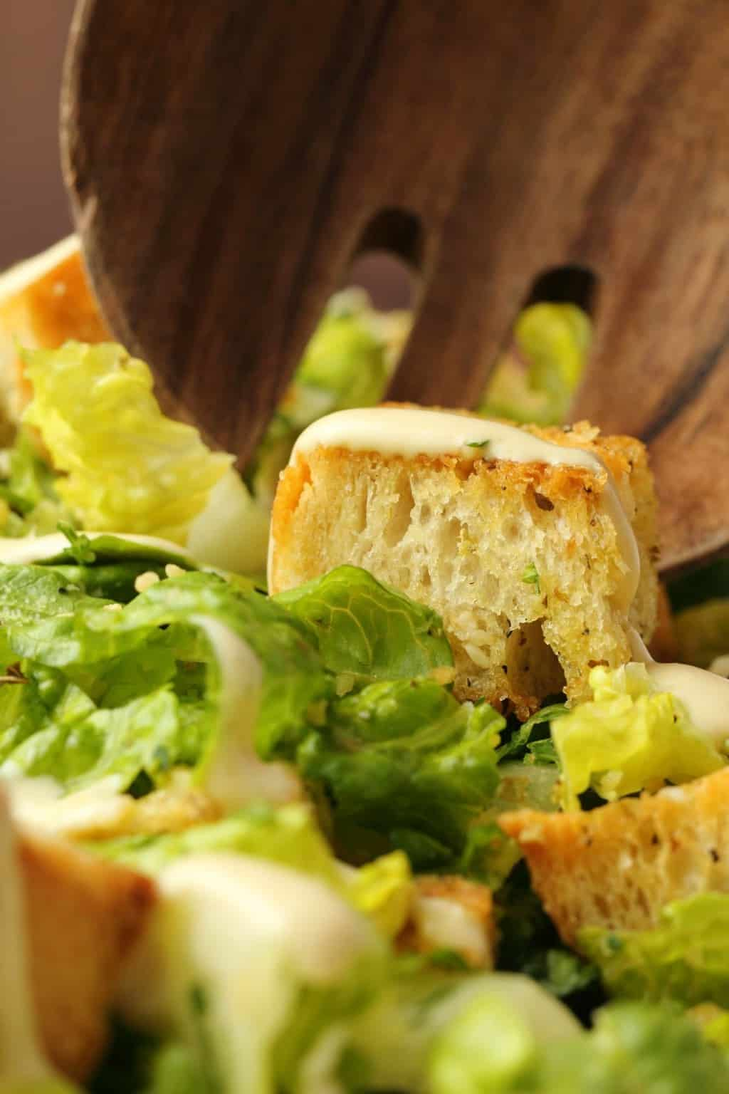 Vegan caesar salad and a wooden salad spoon.