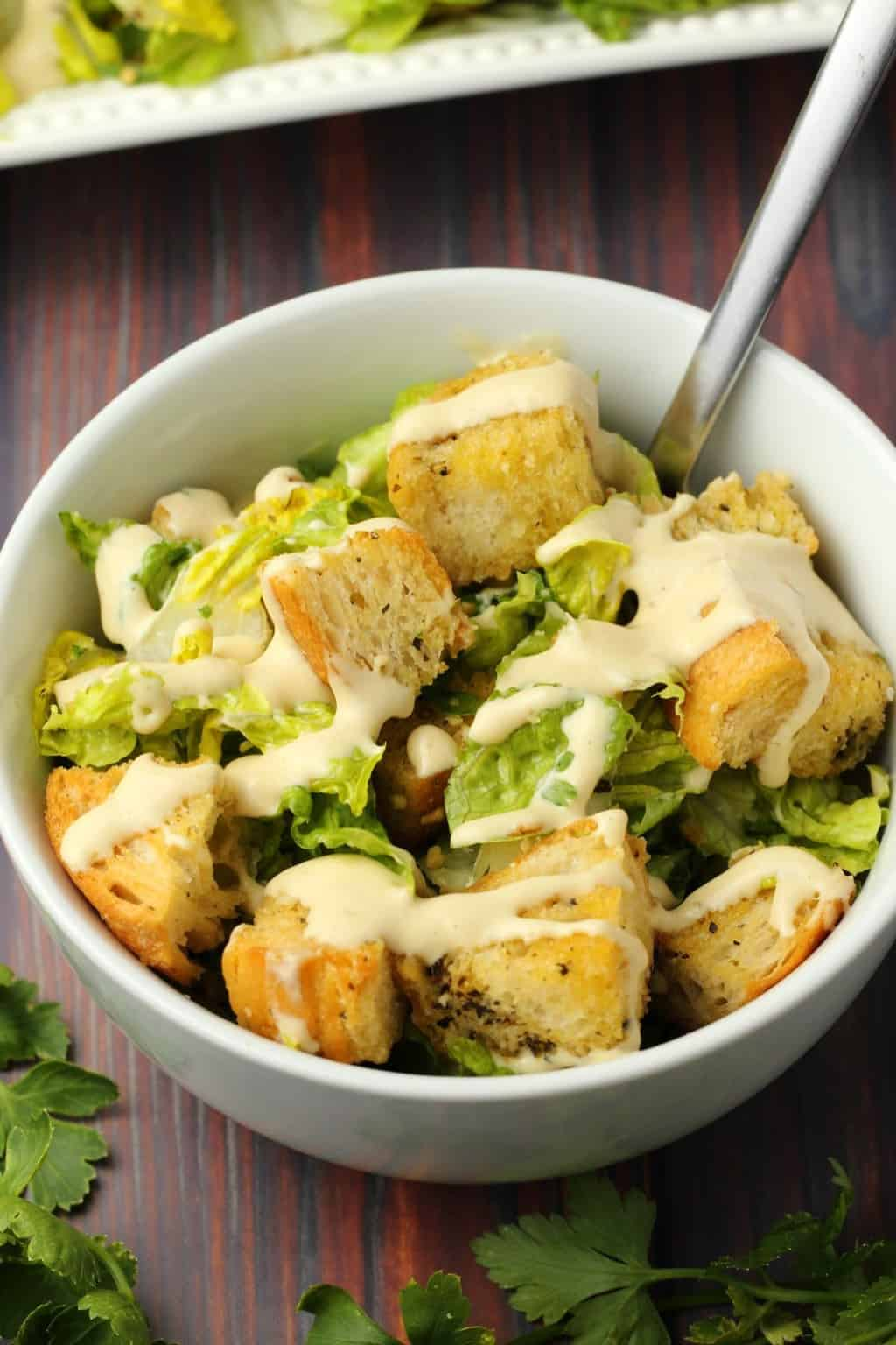 Vegan caesar salad in a white bowl with a spoon.