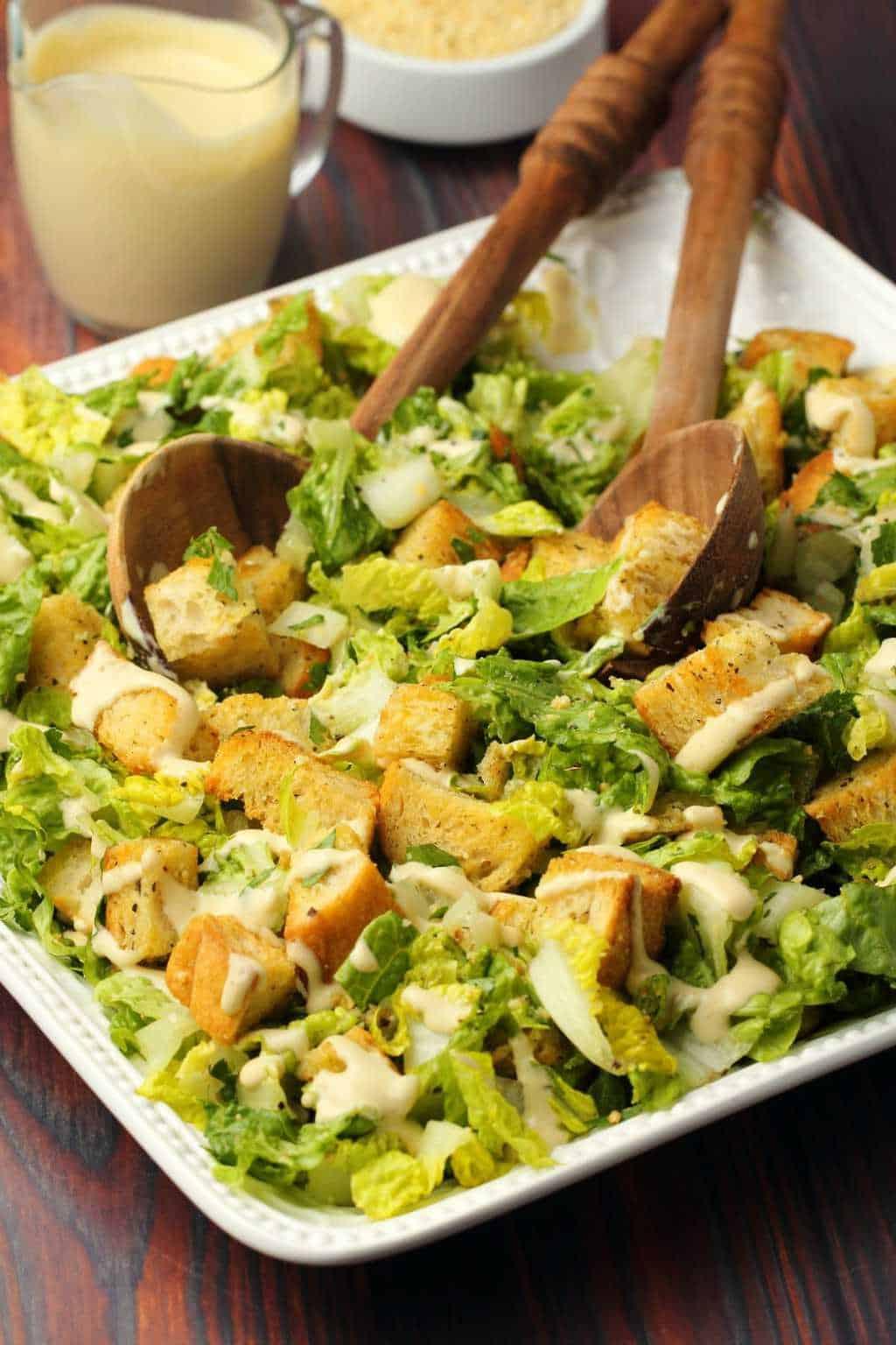 Vegan caesar salad on a white salad platter with wooden salad spoons.