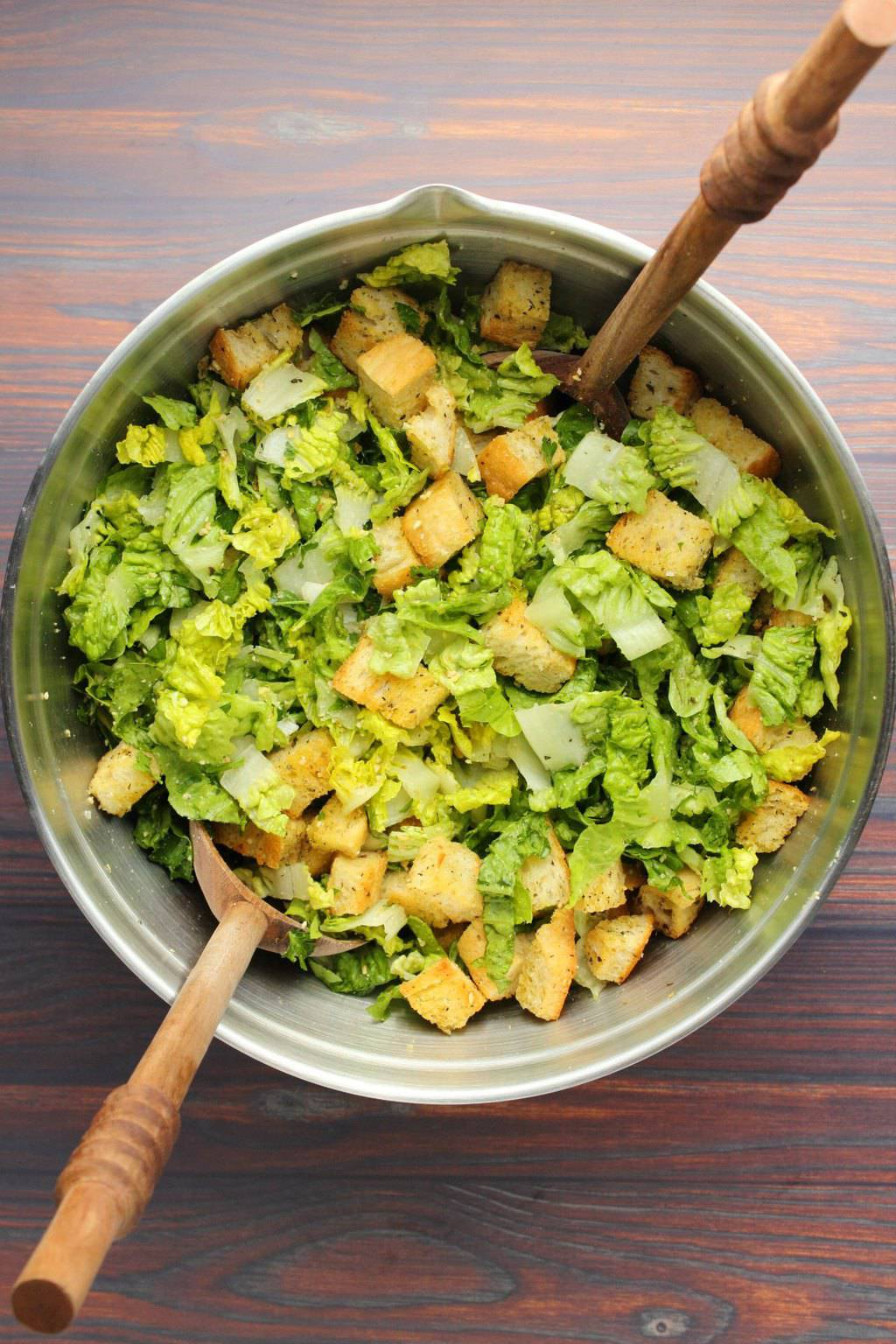 Tossing up a vegan caesar salad in a silver salad bowl with wooden salad spoons.