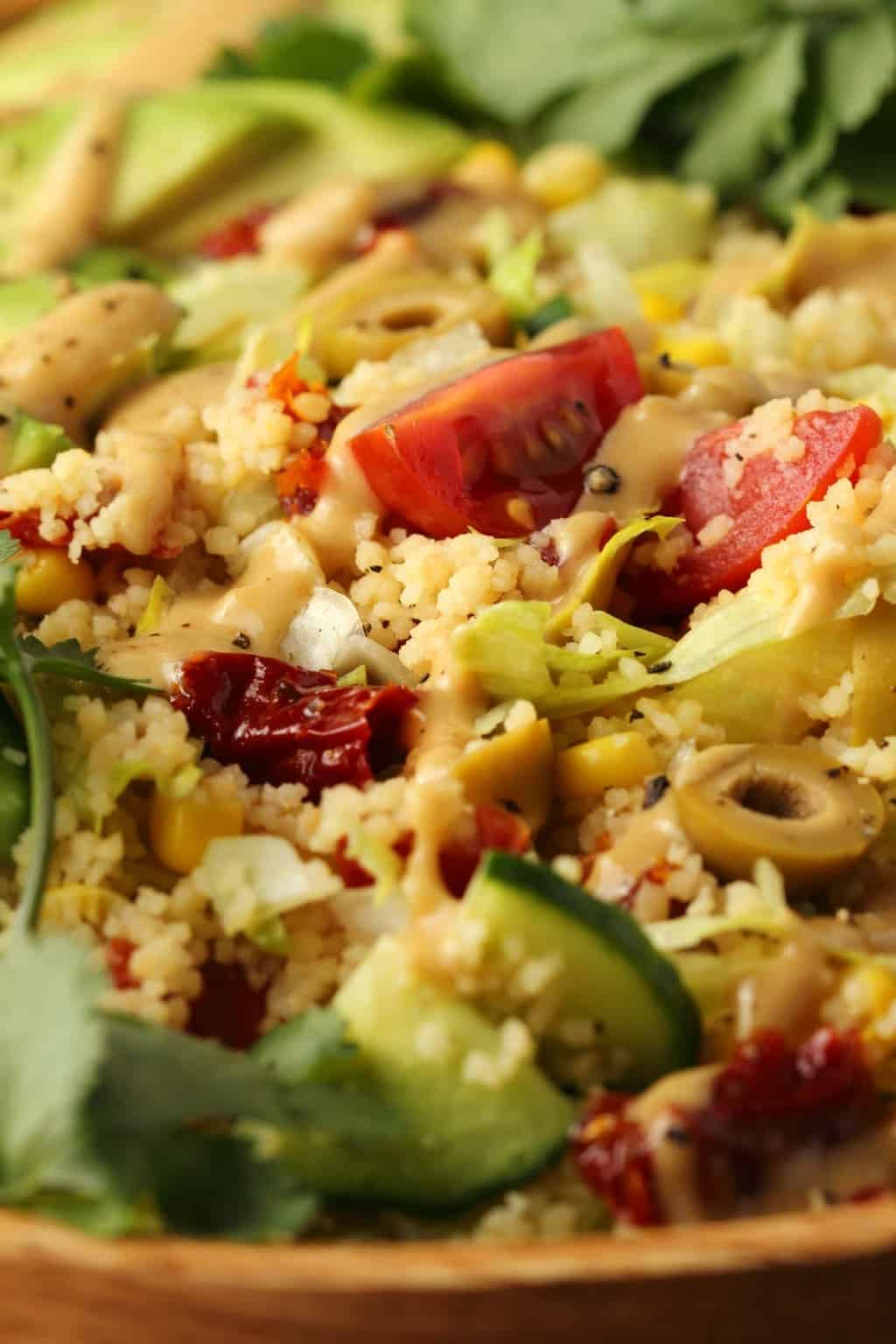 Vegan couscous salad topped with tahini dressing.