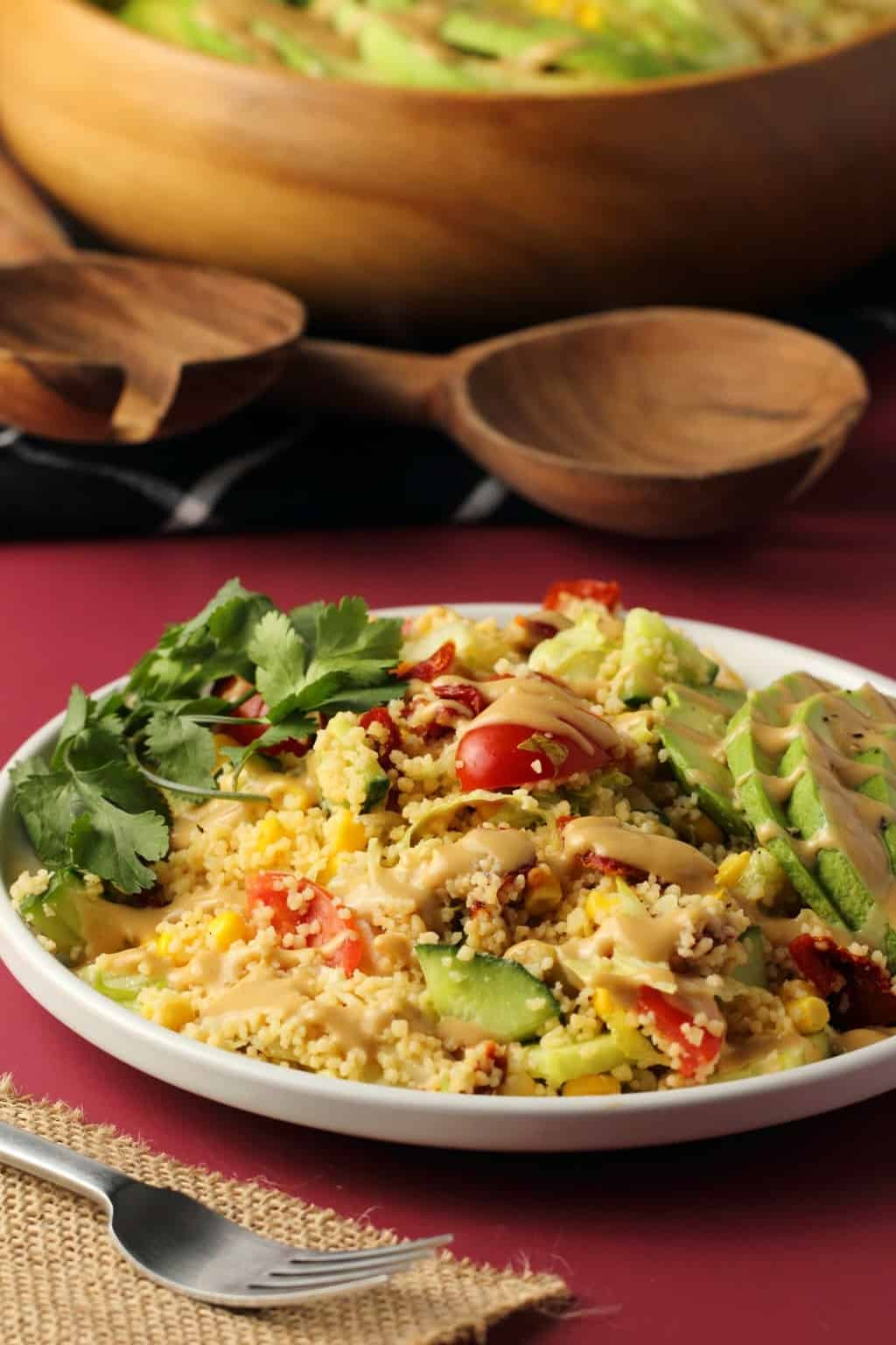 Vegan couscous salad topped with tahini dressing on a white plate.