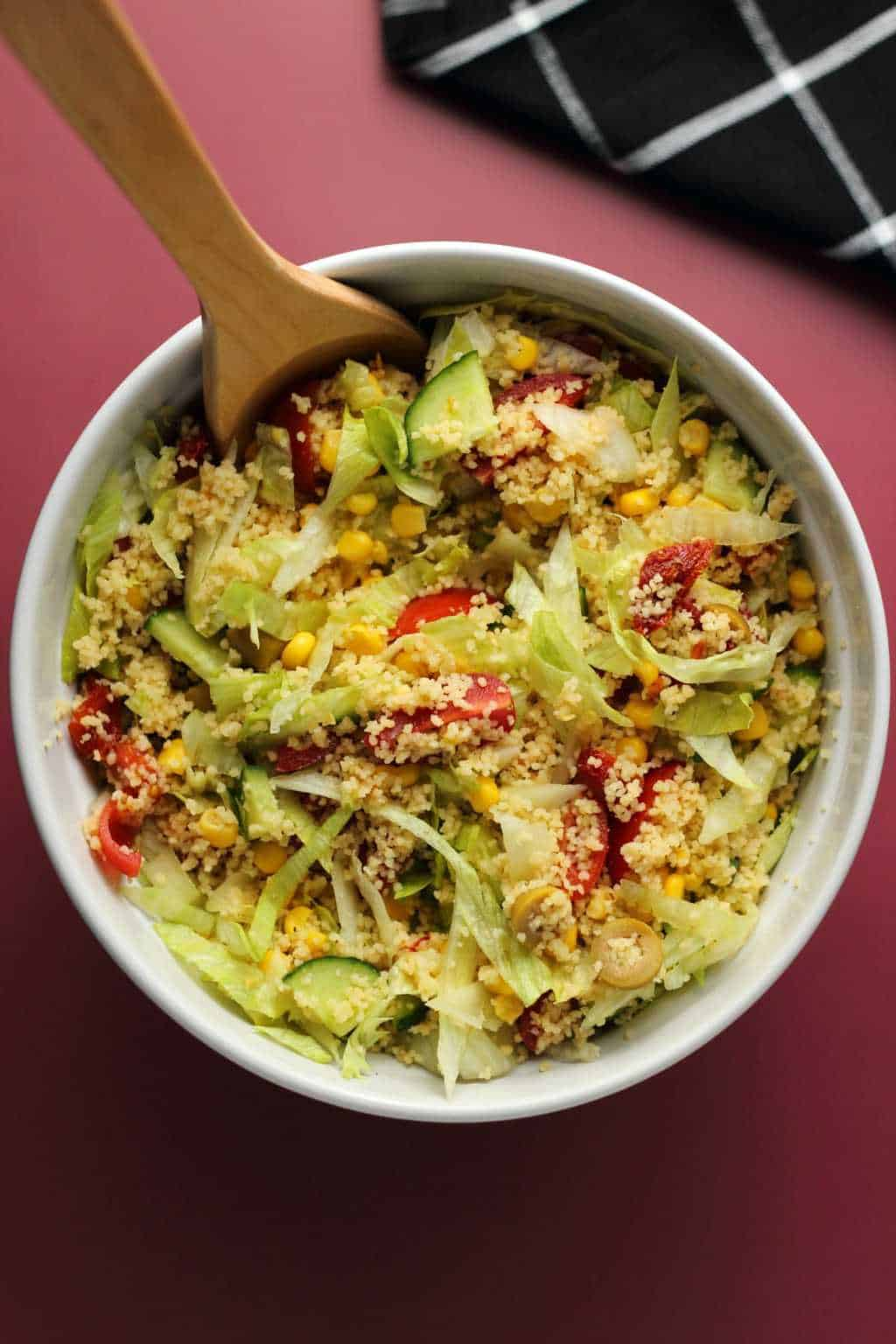 Vegan couscous salad in a white bowl with a wooden spoon.