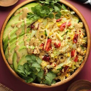 Vegan couscous salad in a wooden serving bowl.