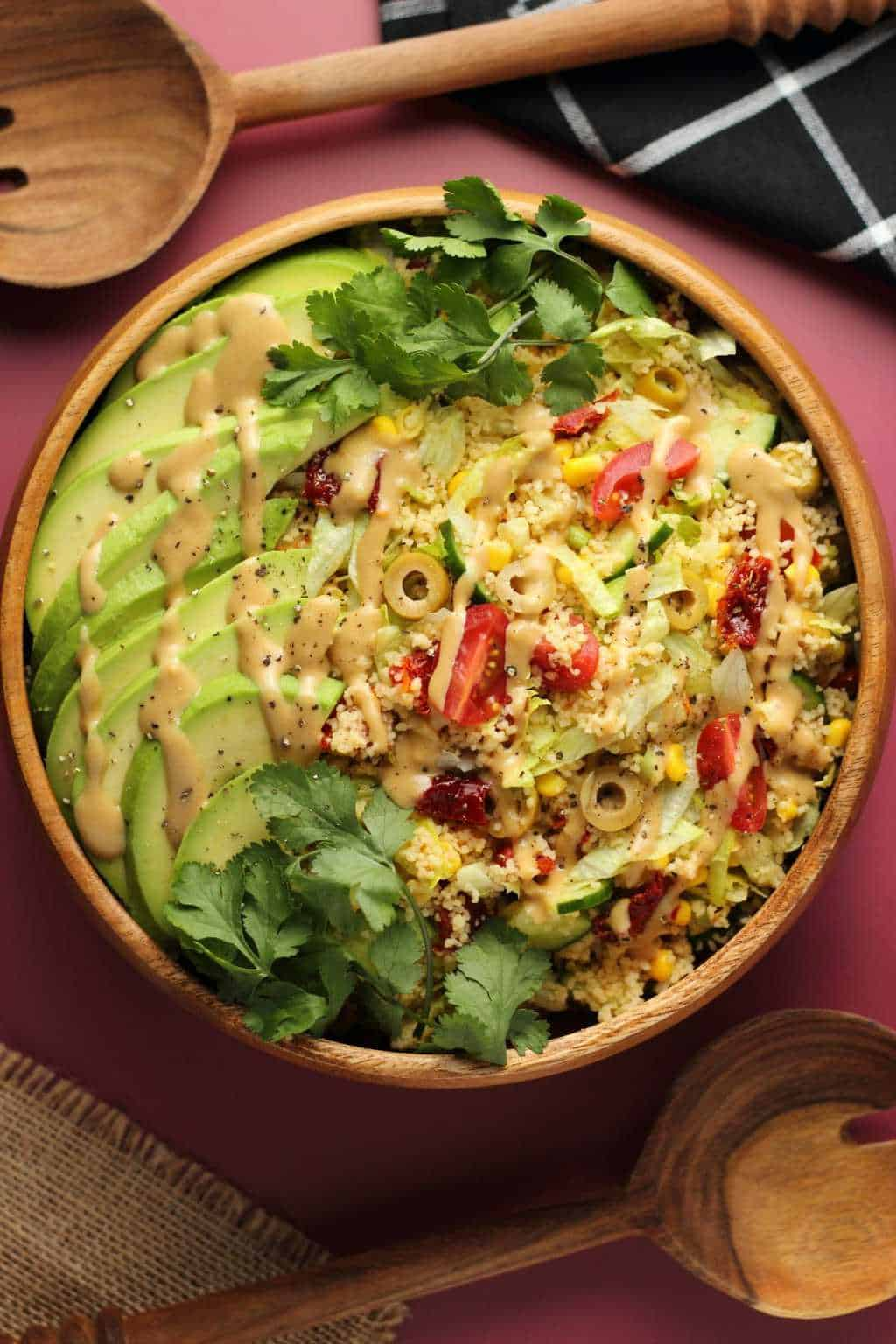 Vegan couscous salad topped with a tahini dressing in a wooden salad bowl.