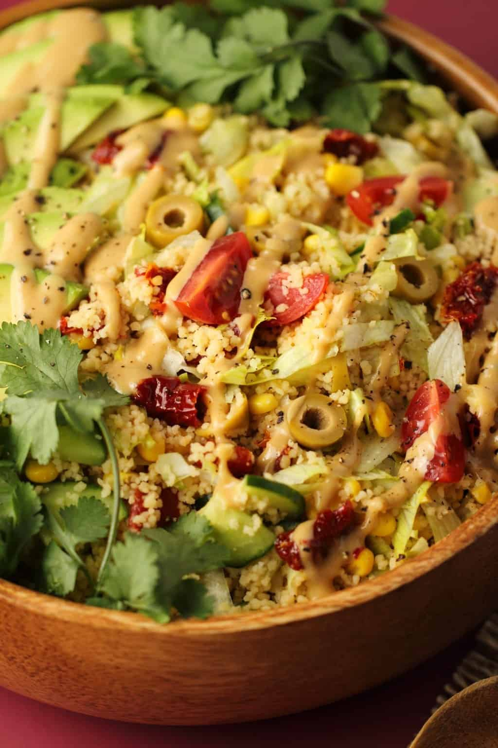 Vegan couscous salad topped with tahini dressing in a wooden salad bowl.