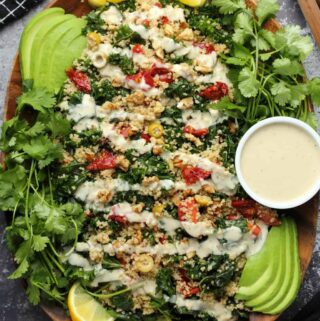 Vegan kale salad topped with drizzled dressing on a wooden serving platter.