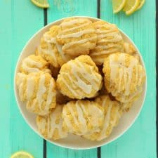 Vegan lemon cookies stacked up on a white plate.