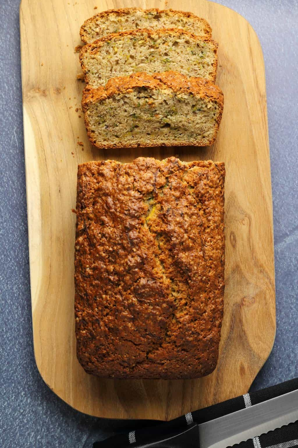 Vegan zucchini bread with the first few slices cut, on a wooden board.