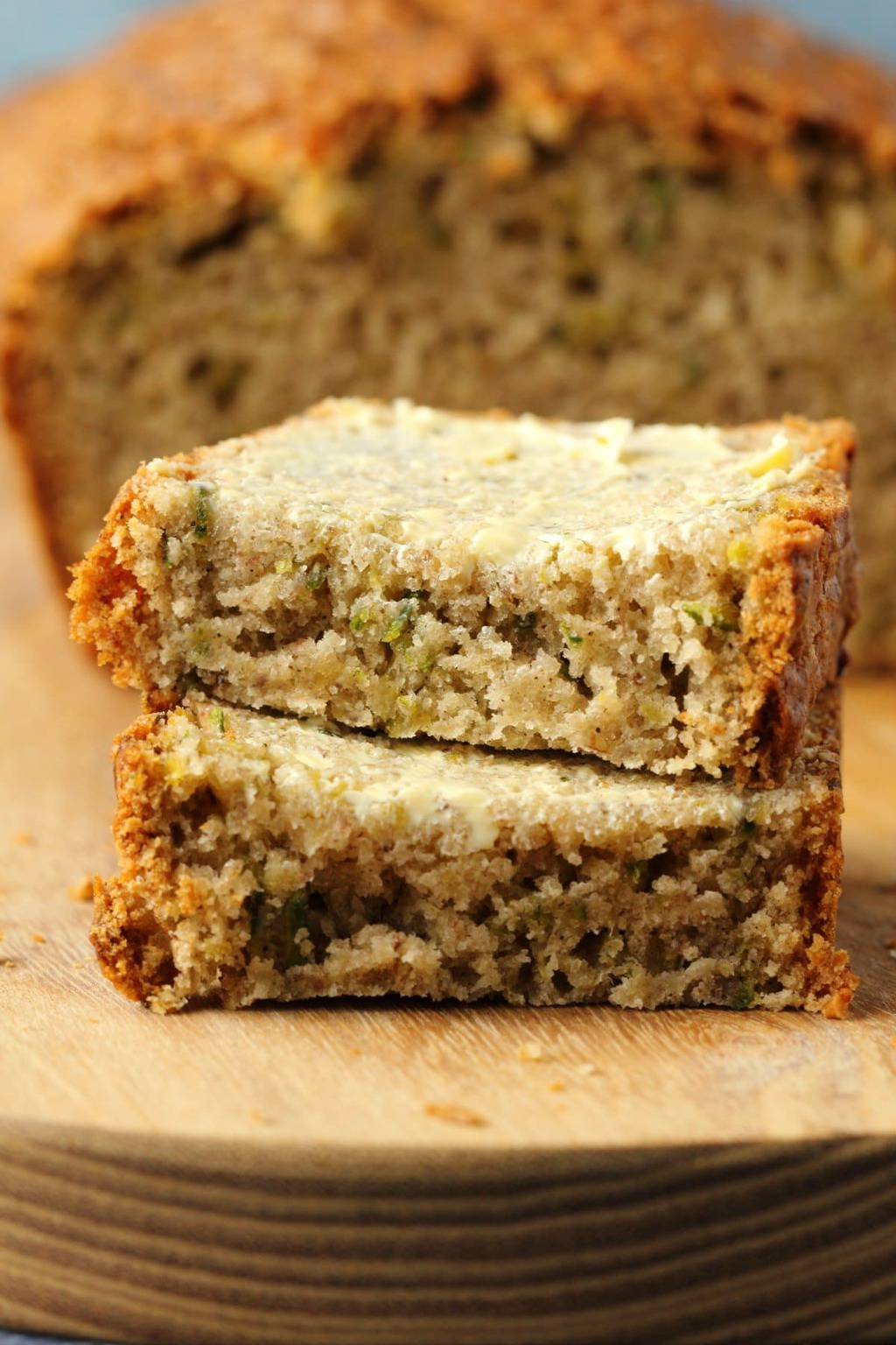 Vegan zucchini bread buttered and sliced in half.
