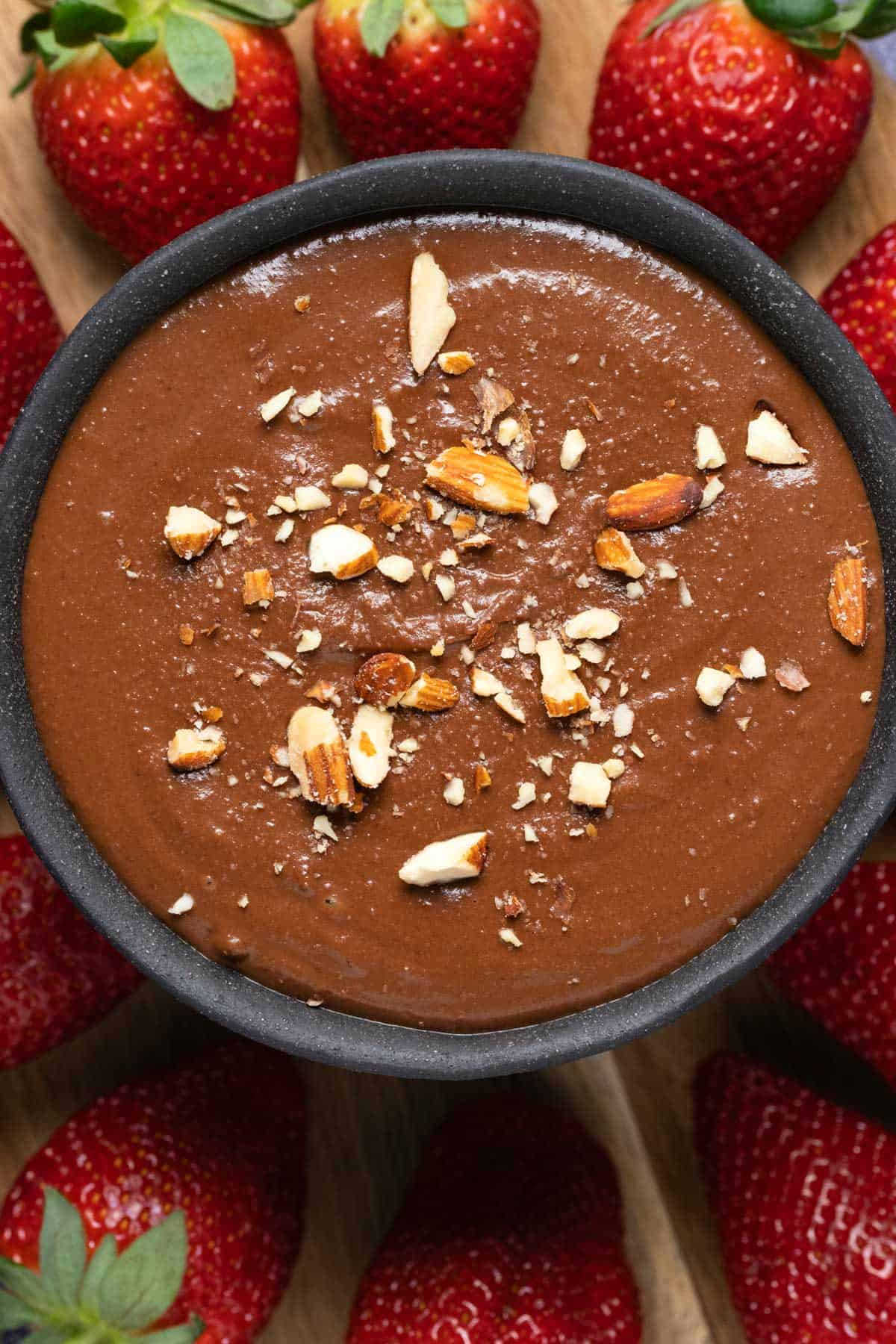 Chocolate hummus topped with chopped almonds in a black bowl.