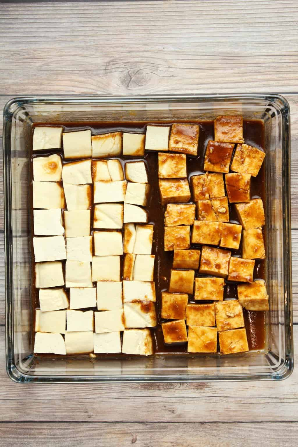 Tofu marinading in a tofu marinade sauce in a glass dish.