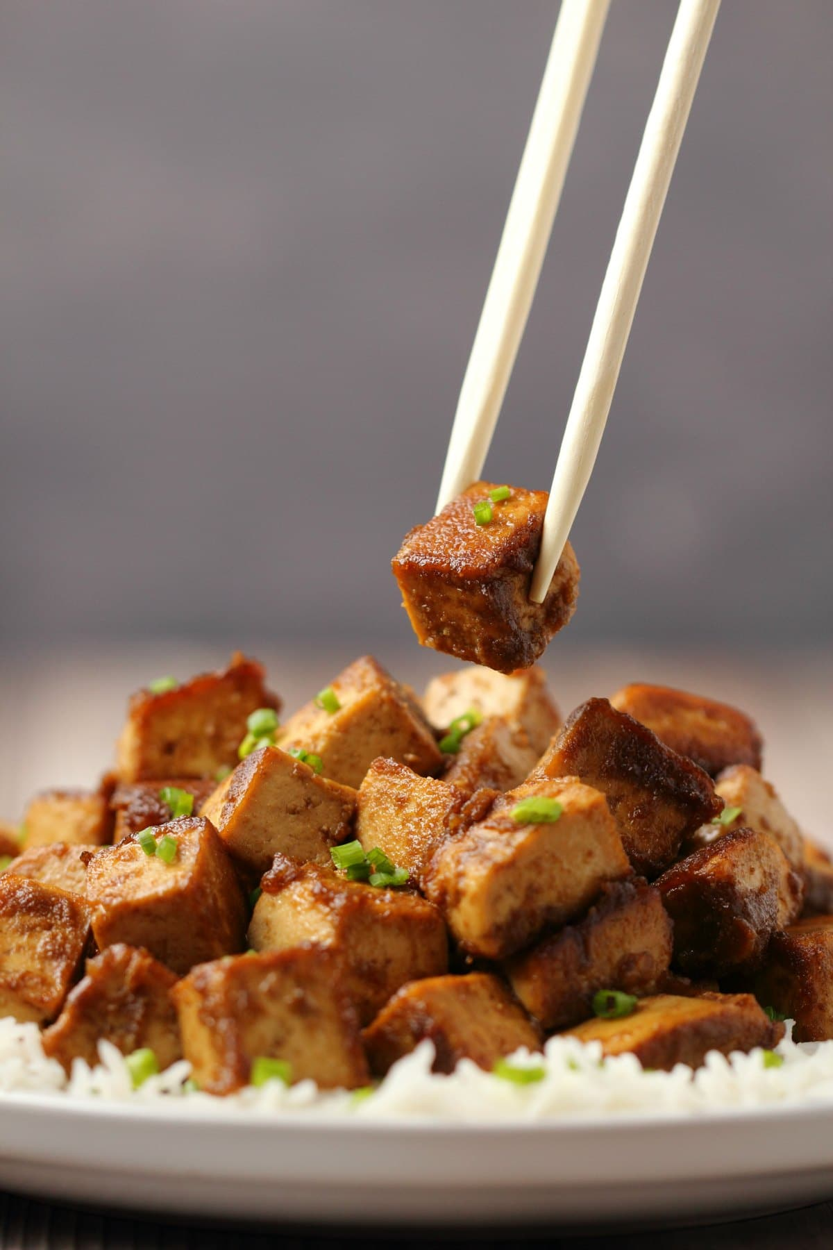 Marinated tofu topped with chopped chives on a bed of rice with chopsticks.