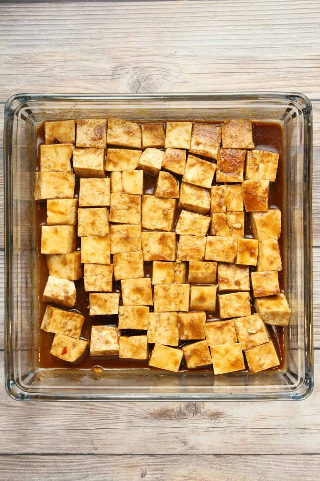 Cubes of tofu marinading in a tofu marinade sauce in a glass dish.