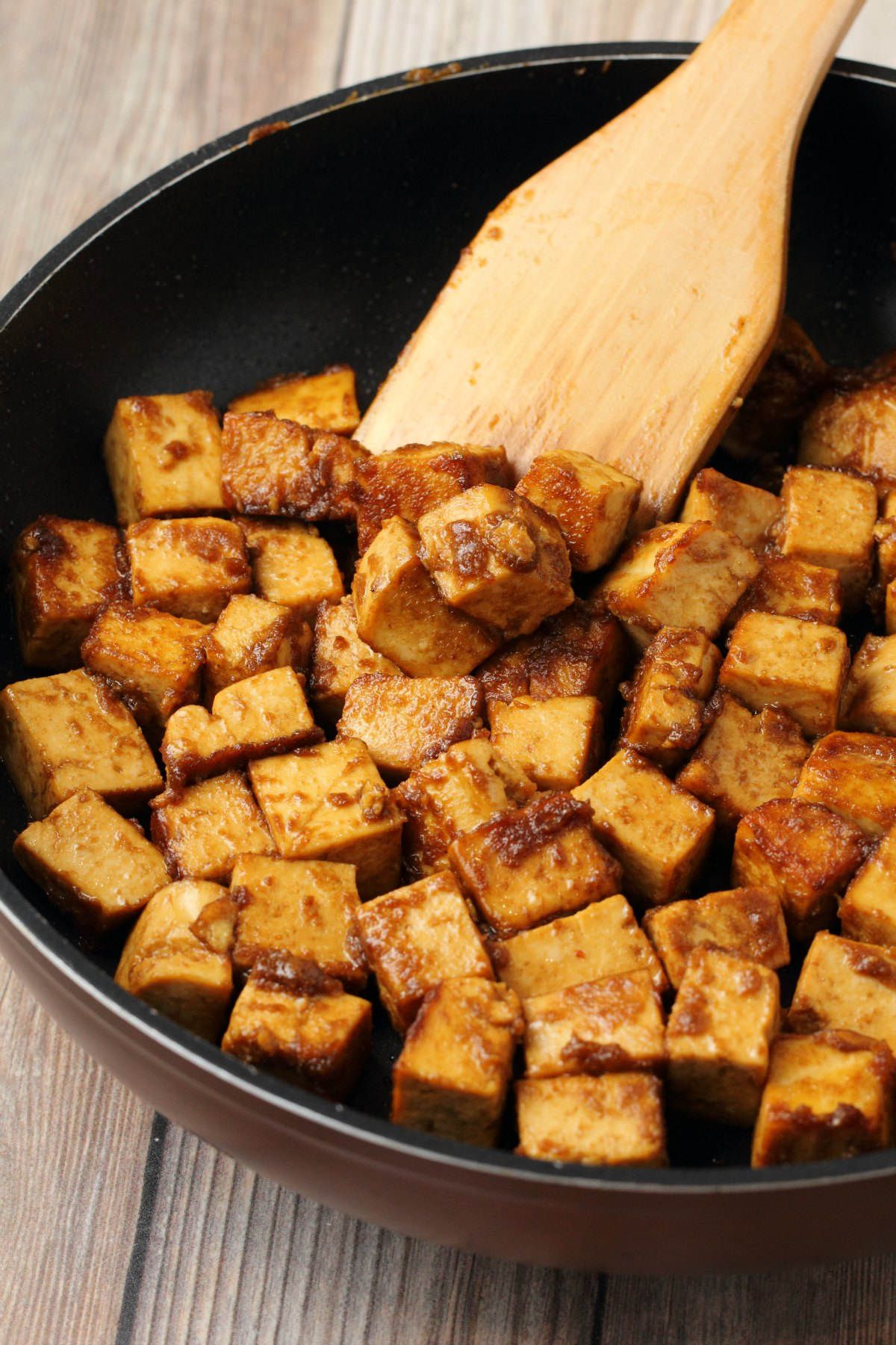 Marinated tofu frying in a pan with a wooden spatula.