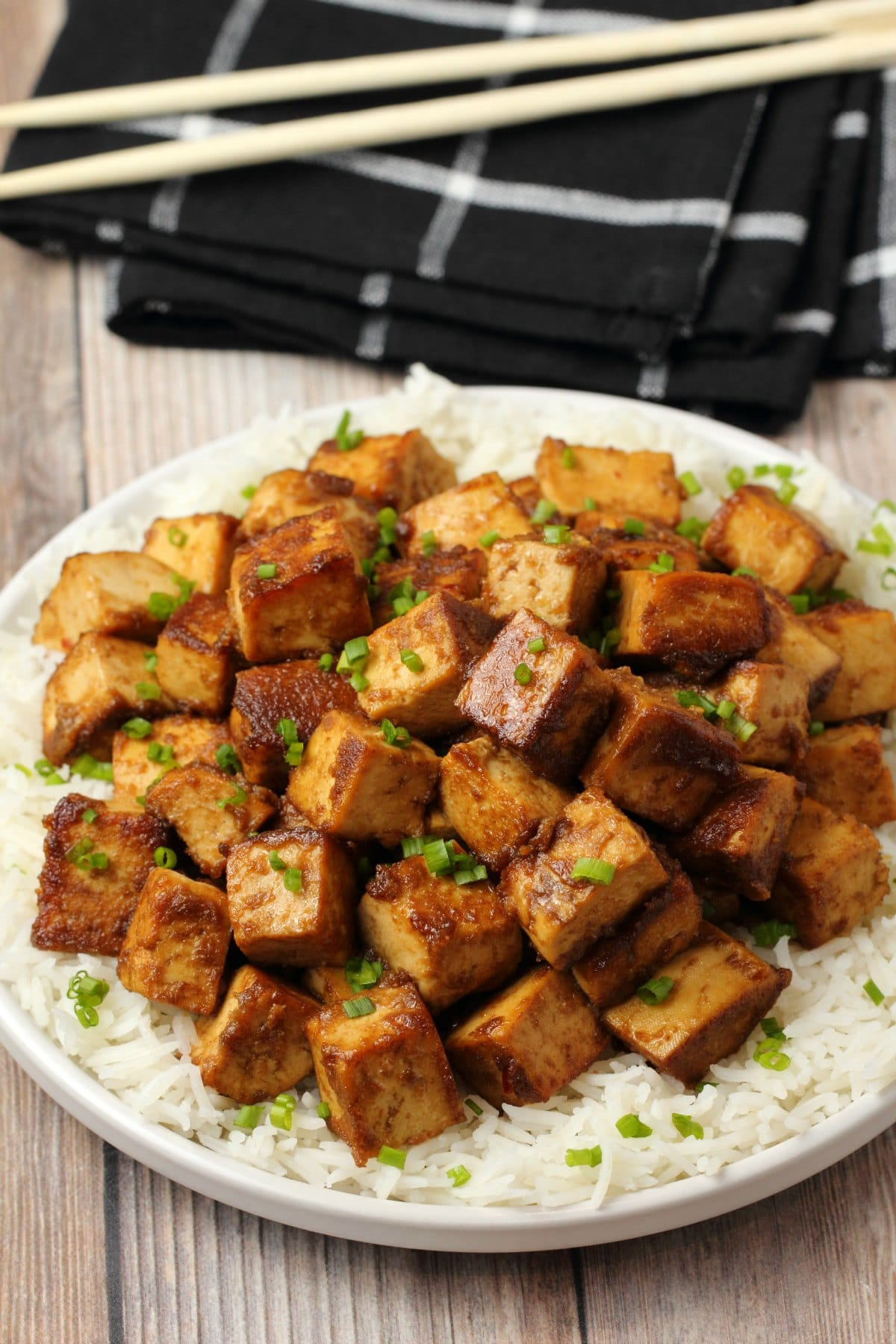 Marinated tofu topped with chopped chives on a bed of rice.