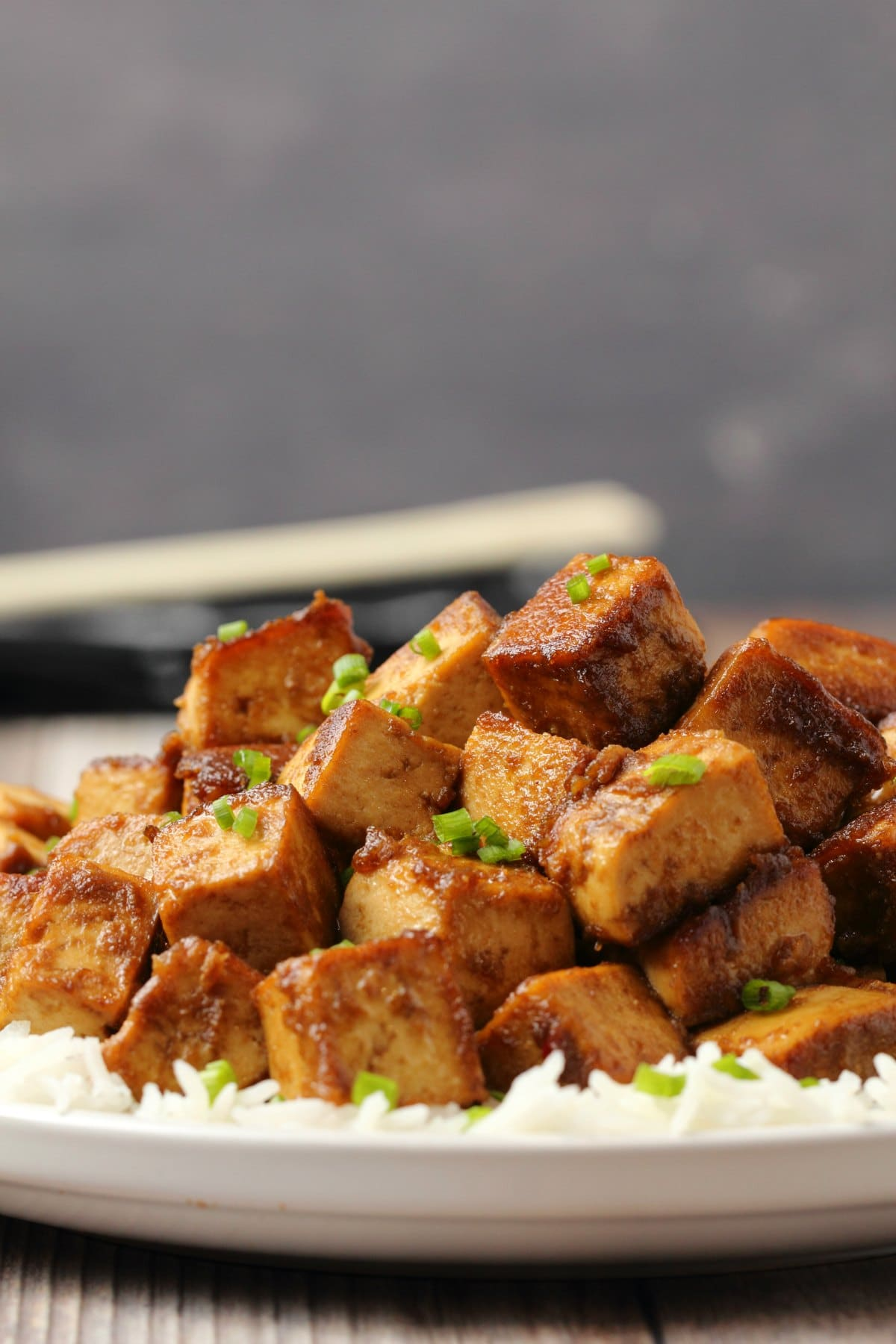 Marinated tofu topped with chopped chives and on a bed of rice.