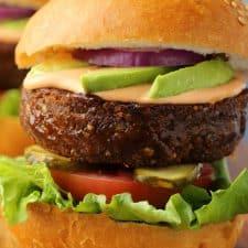 Loaded vegan burger on a wooden board.