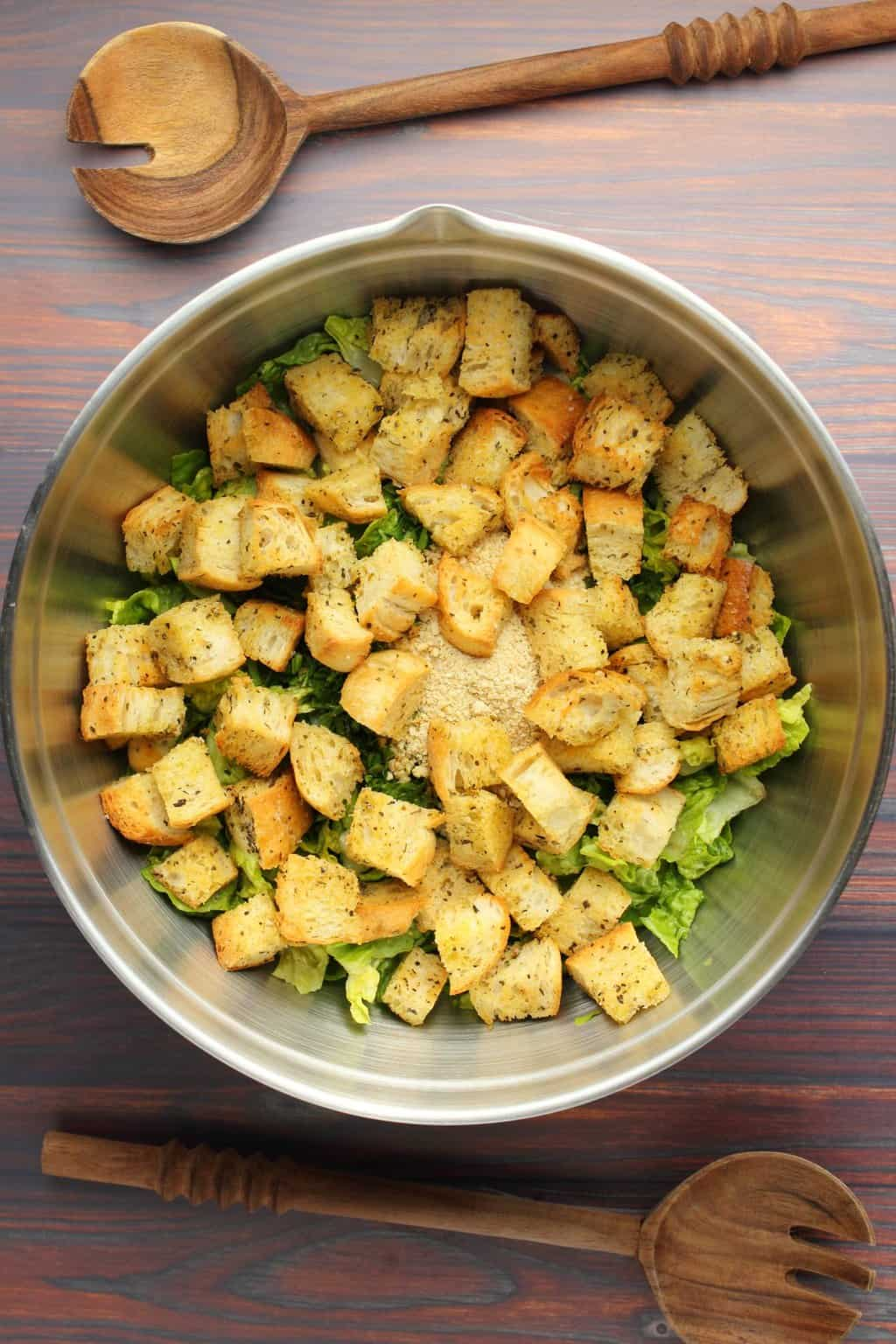 Romaine lettuce, parsley, vegan parmesan and croutons in a salad bowl ready to toss.