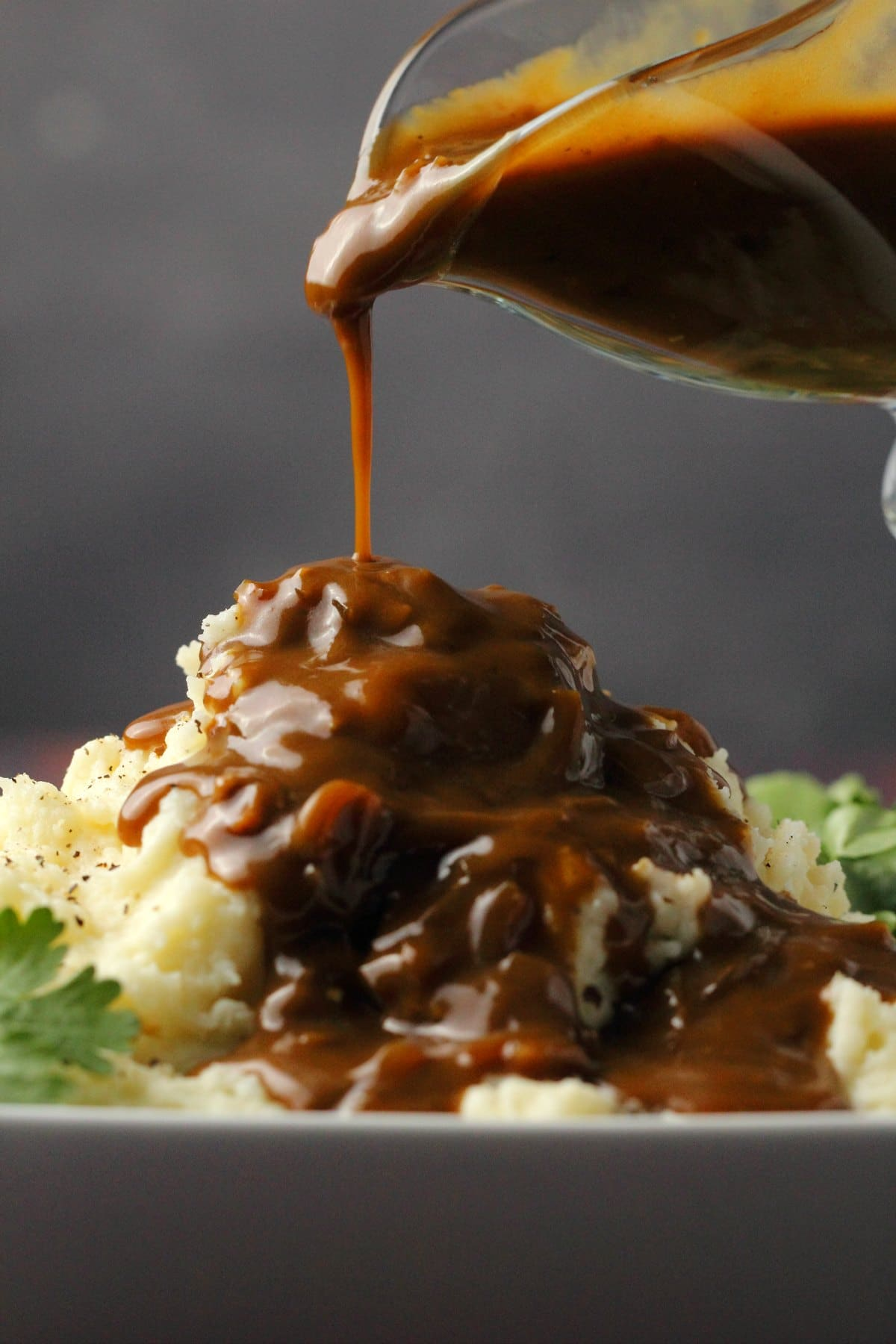 Vegan gravy pouring over mashed potatoes.